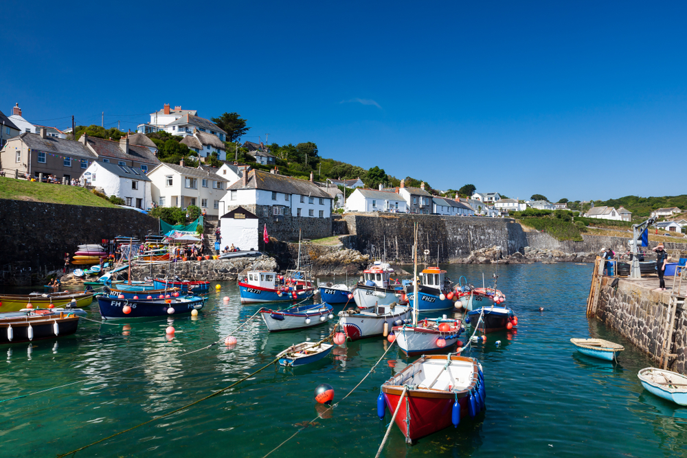 a photo overlooking the bay of Coverack, southern england. The bay is filled with small fishing boats.