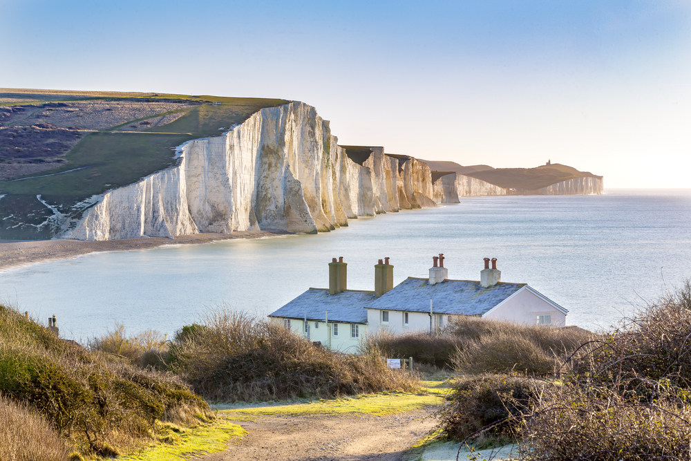a photo of two cottages. Behind them, you can see the seven sisters, a set of chalk cliffs in southern england