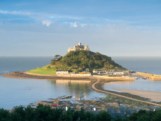 a photo showing St Michael's Mount, a small island with a walkway leading up to it