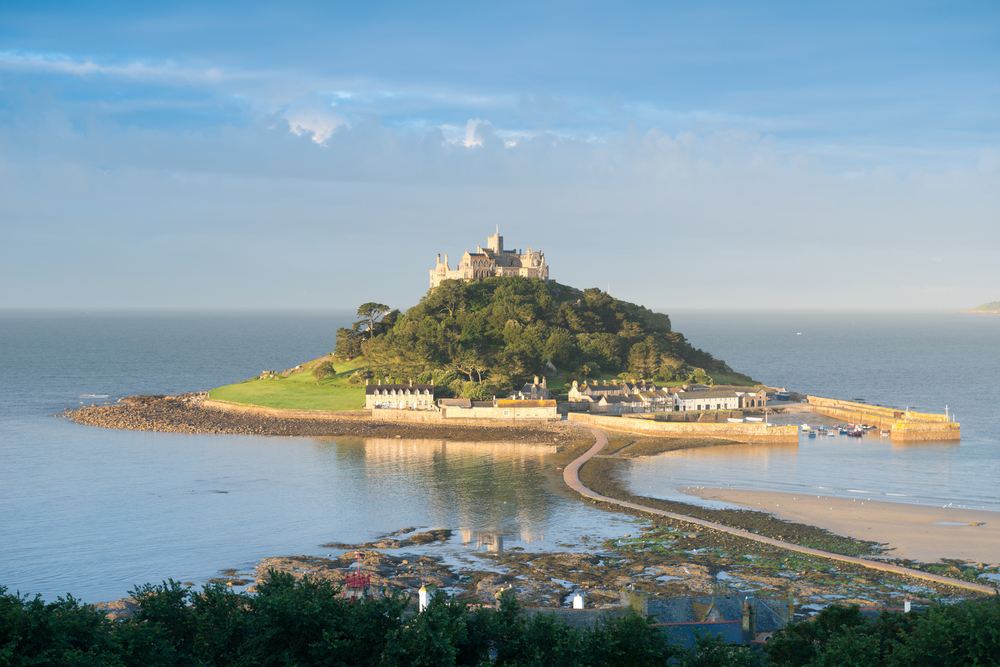a photo showing St Michael's Mount, a small island with a walkway leading up to it.