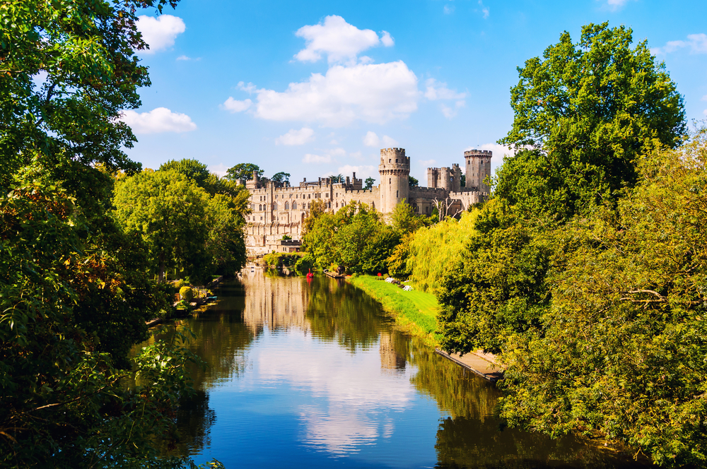 a photo of a lake with the beautiful Warwick Castle in the background, surrounded by trees.