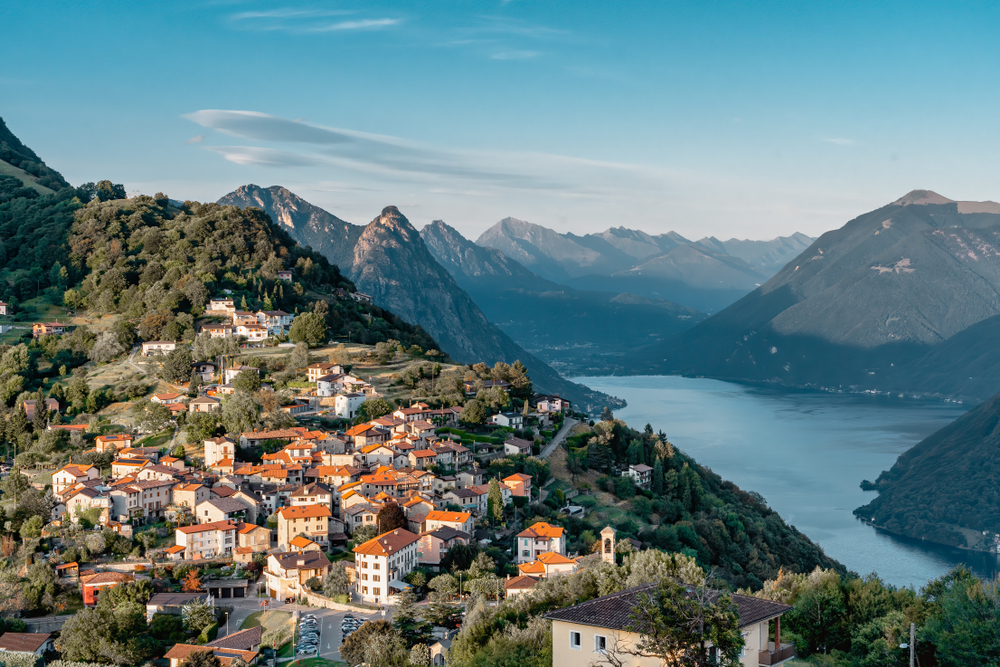 Lugano sits on the edge of Lake Lugano with mountains framing it. one of the most beautiful small towns in Switzerland