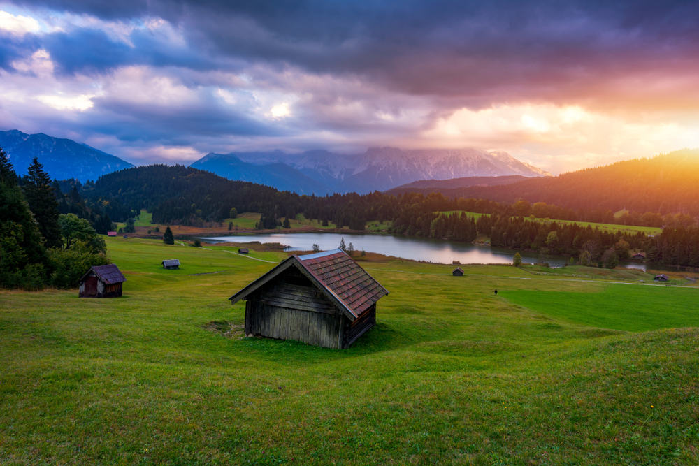 The sun sets behind the mountains in the picturesque valley of Geroldsee