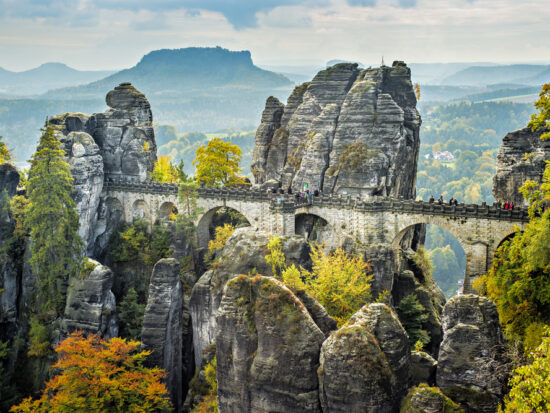 Bastei Bridge seems to float among the rock spires high above the trees.