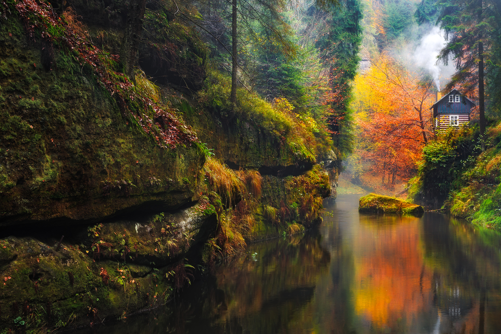 A cabin sits among the autumn foliage at the edge of Kamnitz Gorge, one of the lesser known hidden gems in Germany.