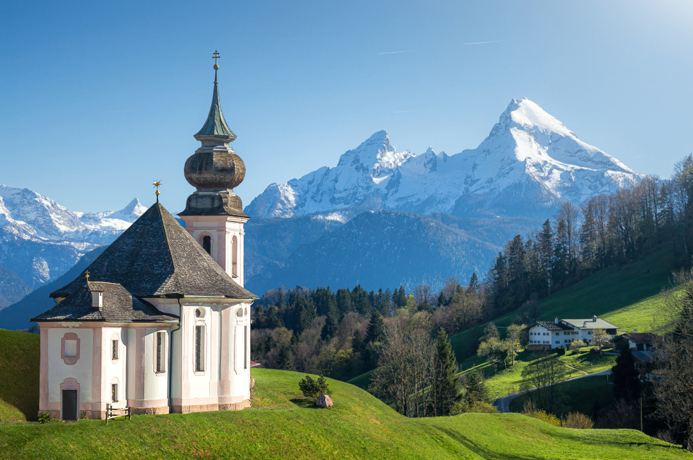 Pilgrimage Church Maria Gern, one of the most gorgeous hidden gems in Germany with snow capped mountains in the distance.