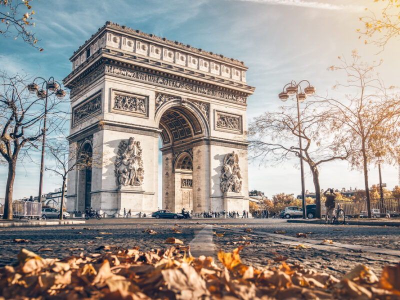 Fall at the Arc De Triomphe. A low shot of the monument with leaves on the ground in front.
