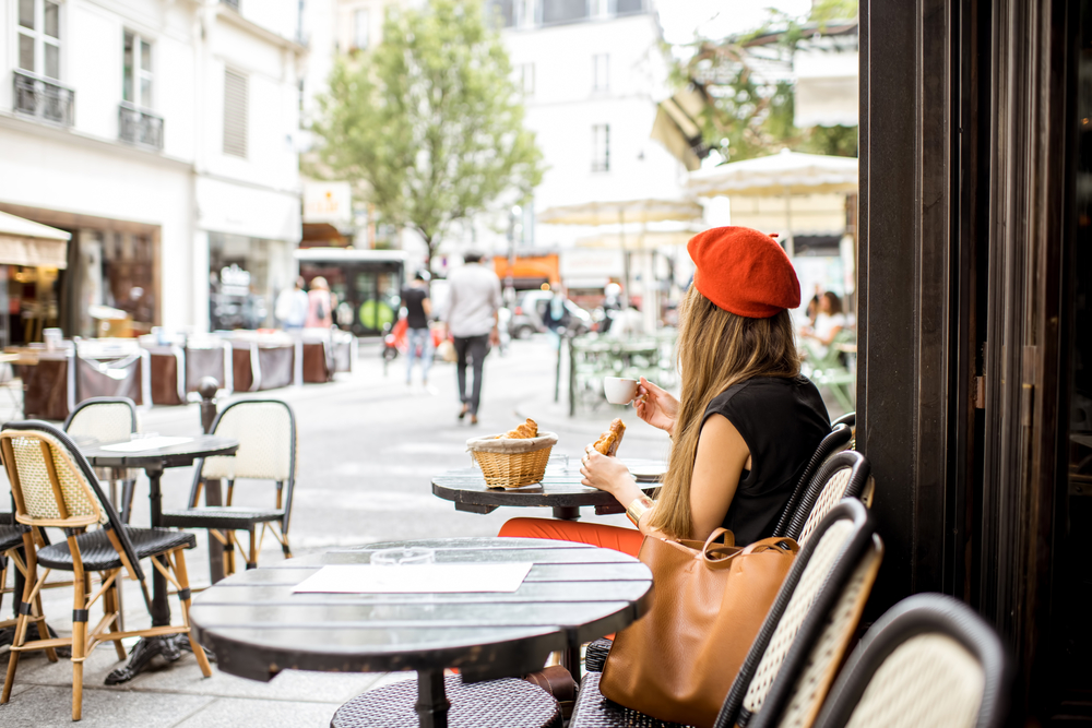 A young stylish woman in a red beret samples a baguette at a Parisian cafe.