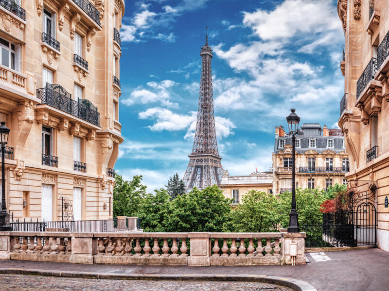 A unique view of the Eiffel Tower in Paris from between two picturesque buildings.