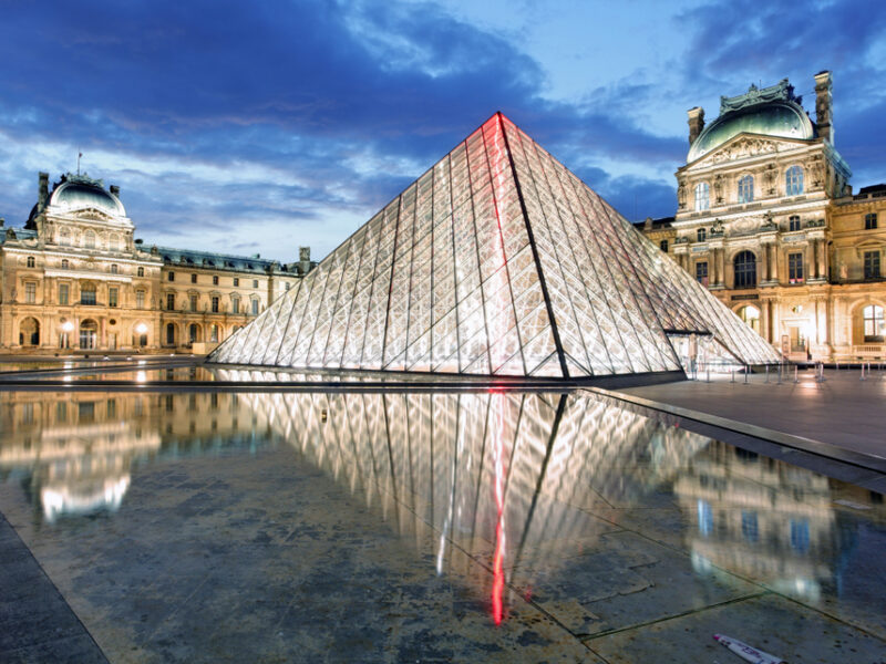 A view of the Louvre Museum in Paris at night all lit up from the inside.