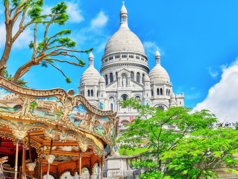 A colorful depiction of Monmarte in Paris with a carousel and cathedral.