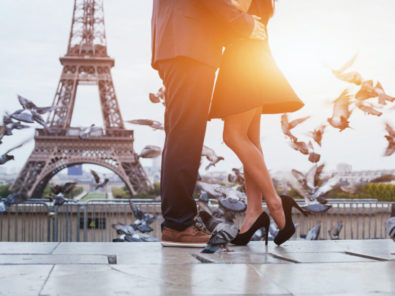 Azoom in shot of two lovers embracing in front of the Eiffel Tower in Paris at sunset.