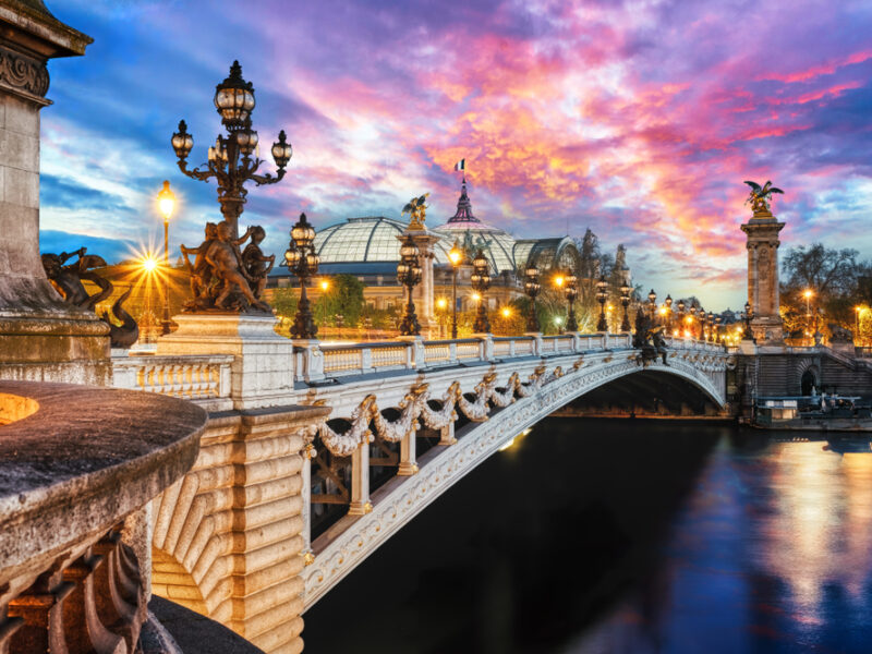 A twilight view of the seine in Paris with streetlamps lining a decorative bridge.