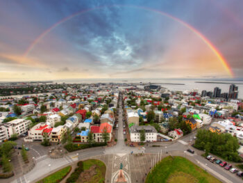 An overhead shot of Reykjavik Iceland with a rainbow backdrop.