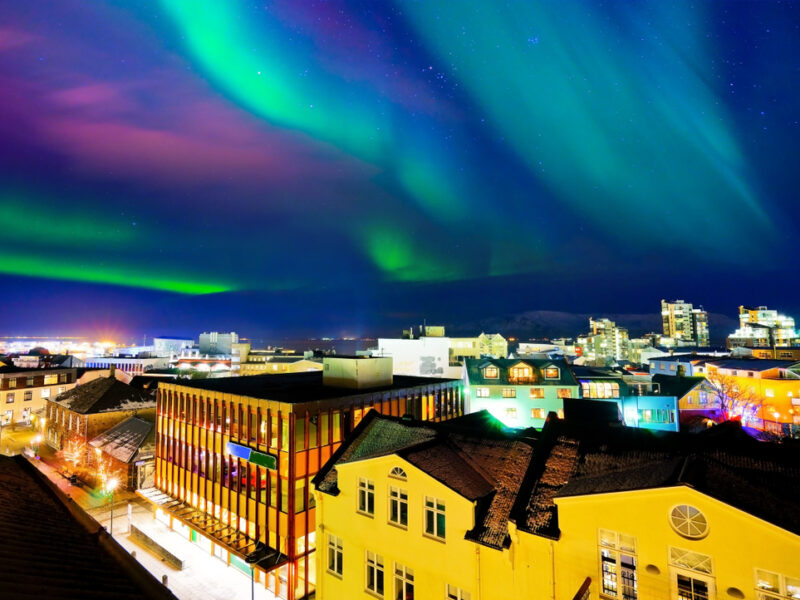 The streets of Reykjavik lit by purple, green and blue Northern Lights.