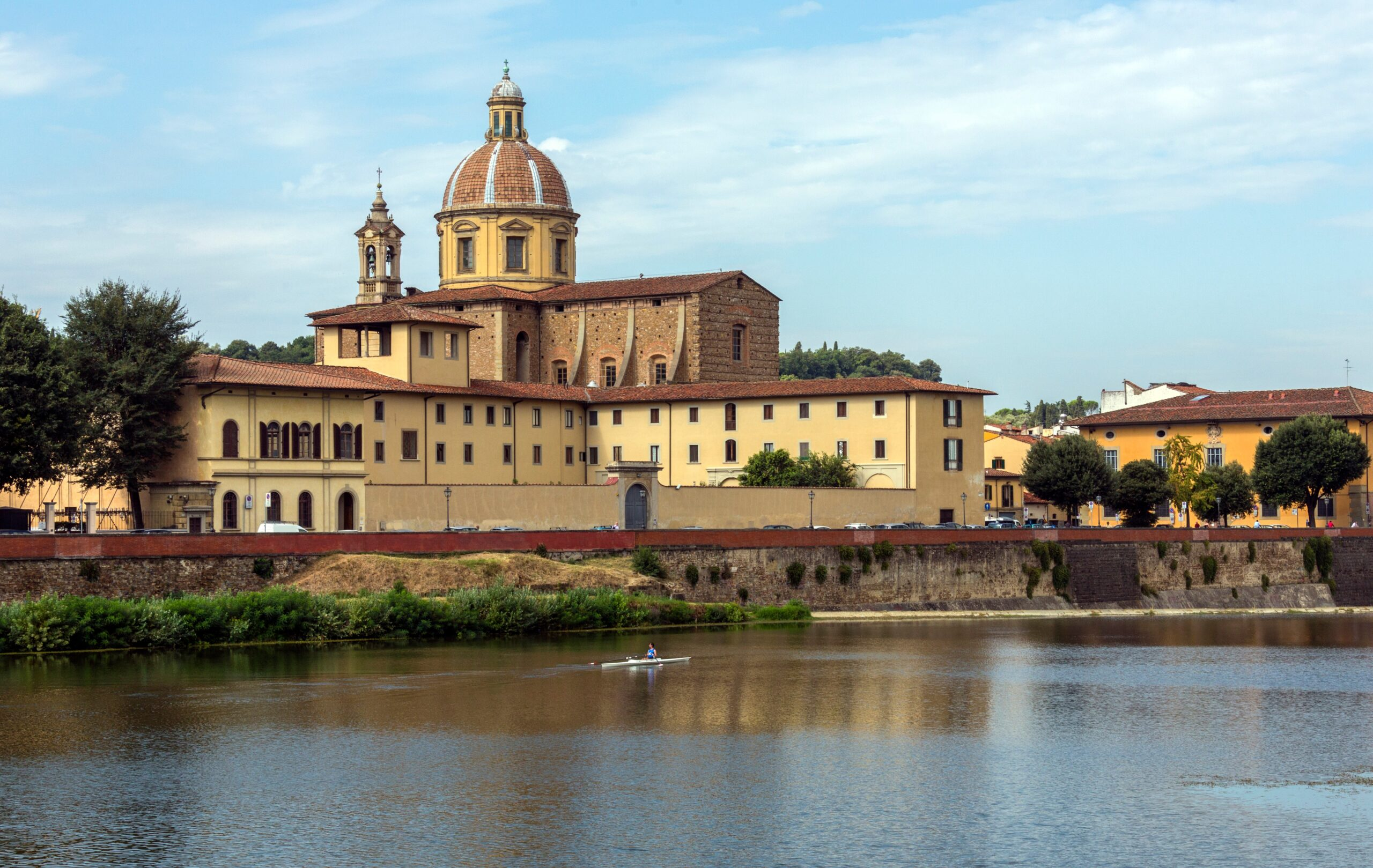 Photo featuring the Arno River with Santo Spirito Church in the background in Florence Italy.