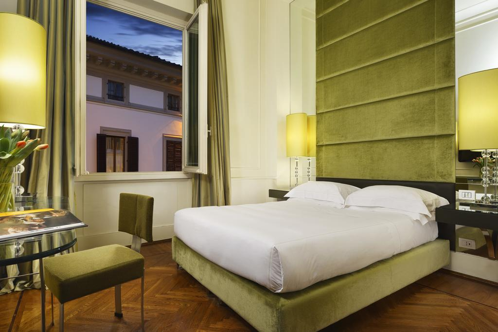 Photo of guest room at Brunelleschi Hotel one of the best places to stay in Florence Italy. Photo features a bed with white linens. The room has leaf green accents.