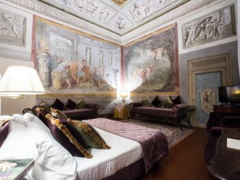 Photo of guest room at Hotel Burchianti in Florence Italy. Room is ornate a large bed with white linen sheets and plum and green velvet pillows. Plum velvet cushioned benches line the room. Large frescoes are on the walls and ceiling.
