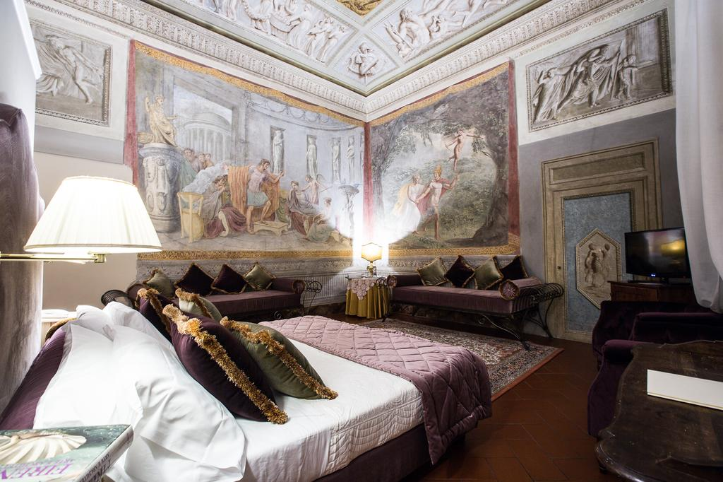 Photo of guest room at Hotel Burchianti one of the best places to stay in Florence. Room is ornate a large bed with white linen sheets and plum and green velvet pillows. Plum velvet cushioned benches line the room. Large frescoes are on the walls and ceiling.