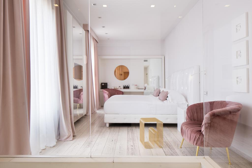 Photo of guest room at Hotel Home Florence one of the best places to stay in Florence. Features a modern room with blush and white curtains. There is a glass partition with a blush velvet arm chair on the other side.