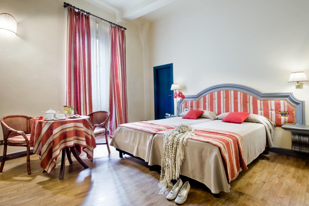 Photo of guest room at Hotel Unicorno a Florence accommodation. Features a bed with red, white, and tan linens. Red, tan, and white striped curtains are hanging in front of a large window. There is a small cozy table with two chairs.