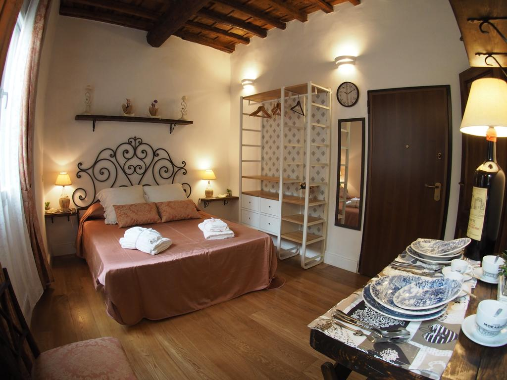 Photo of apartment Nido de Pitti in Florence Italy. Room features a chic Italian country side vibe. Bed has a wrought iron frame with a whimsical curly head board design. A satin duvet is on the bed with neatly appointed guest towels. A breakfast nook is seen in the foreground with a table set with plates and silverware. There is a lamp made from a wine bottle.