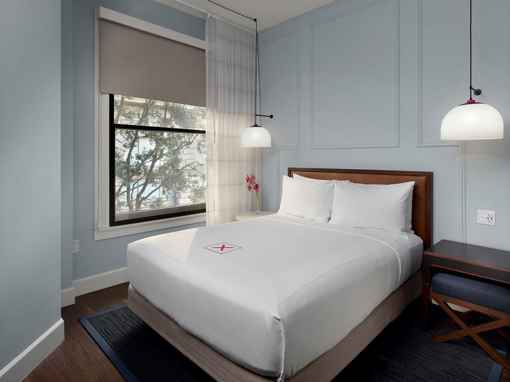 Photo of guest room at Axiom Hotel located in San Francisco. One of the best places to stay in San Francisco. Features a bed with white linens and a window with a tree outside.