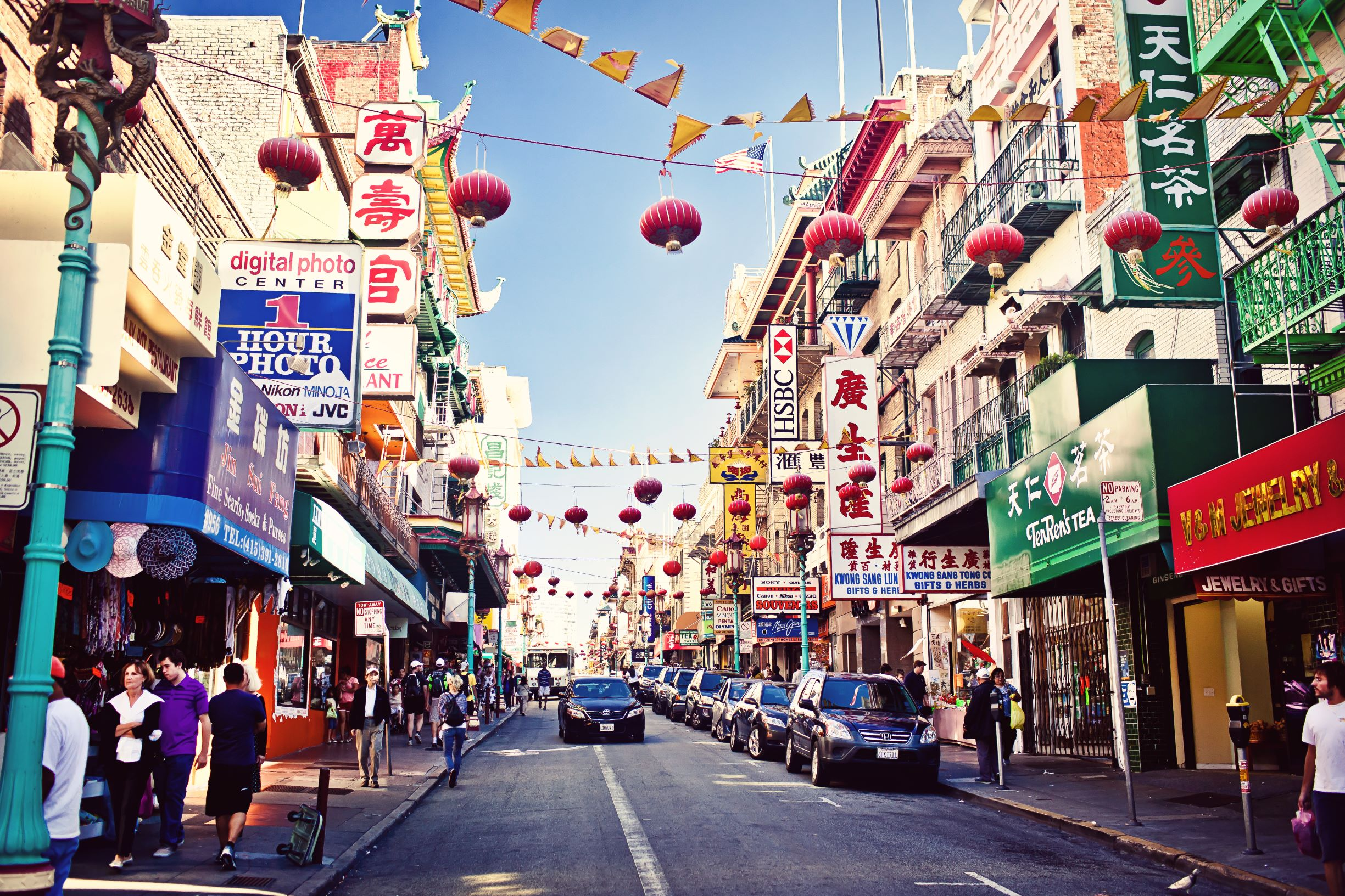 Photo of Chinatown, one of the best places to stay in San Francisco. Photo features a street view of different shops and restaurants with a road in the middle. Lanterns are strung above the street.