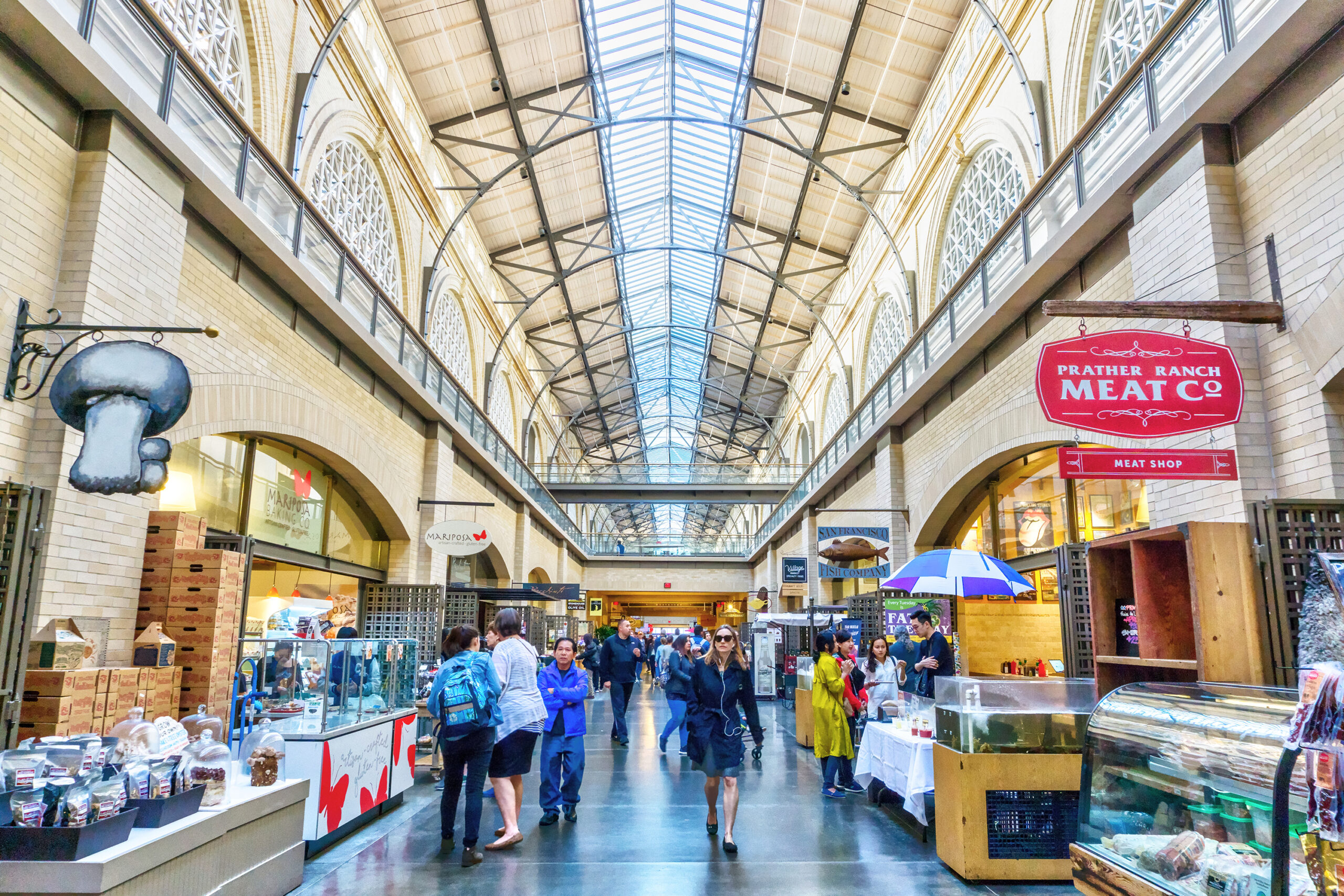 Photo of the inside of the Ferry Building in San Francisco featuring multiple vendors and tourists.