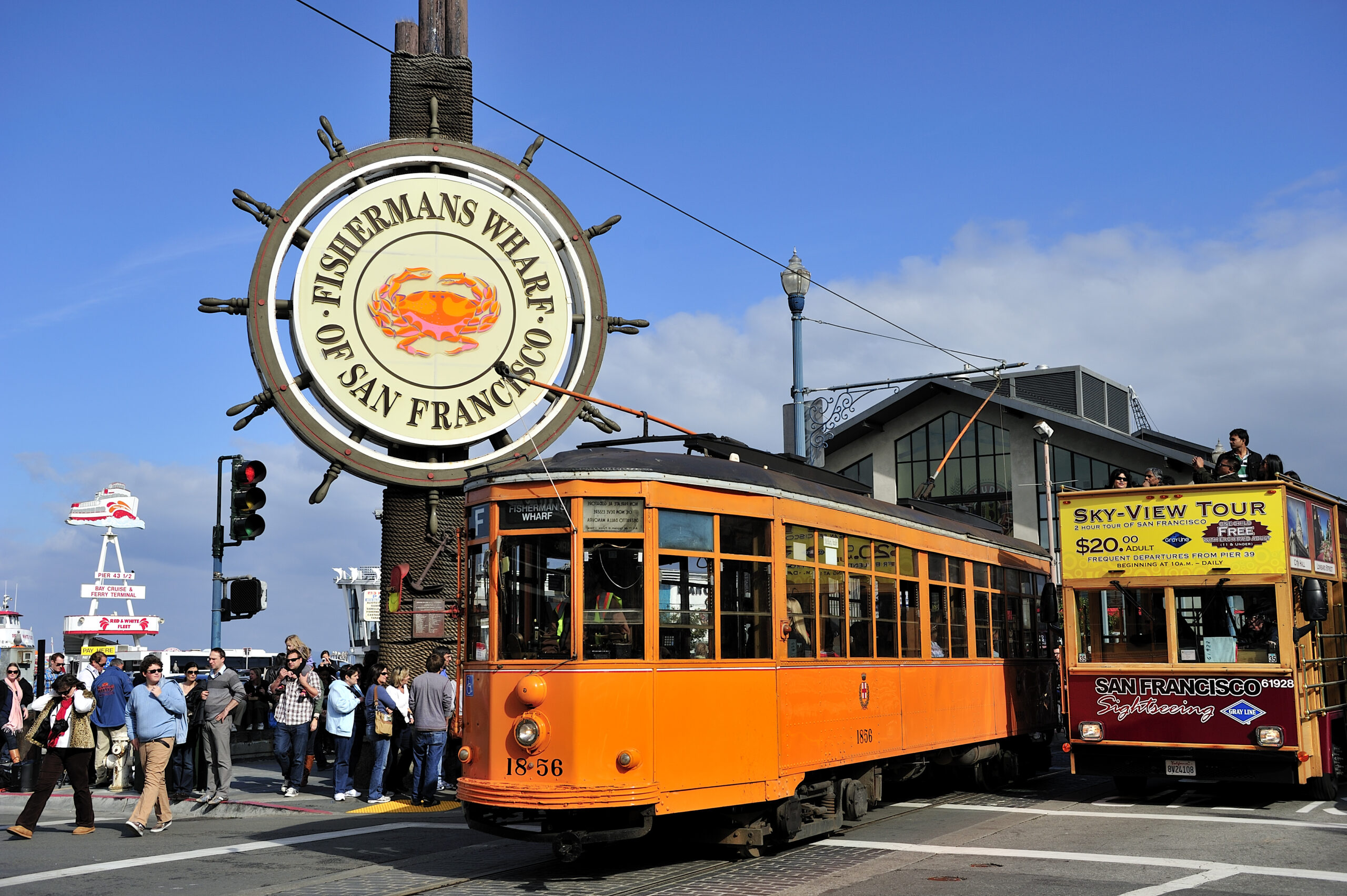 Photo of Fisherman's Wharf, one of the best places to stay in San Francisco. Photos features iconic Fisherman's Wharf sign with two cable car along the sidewalk.