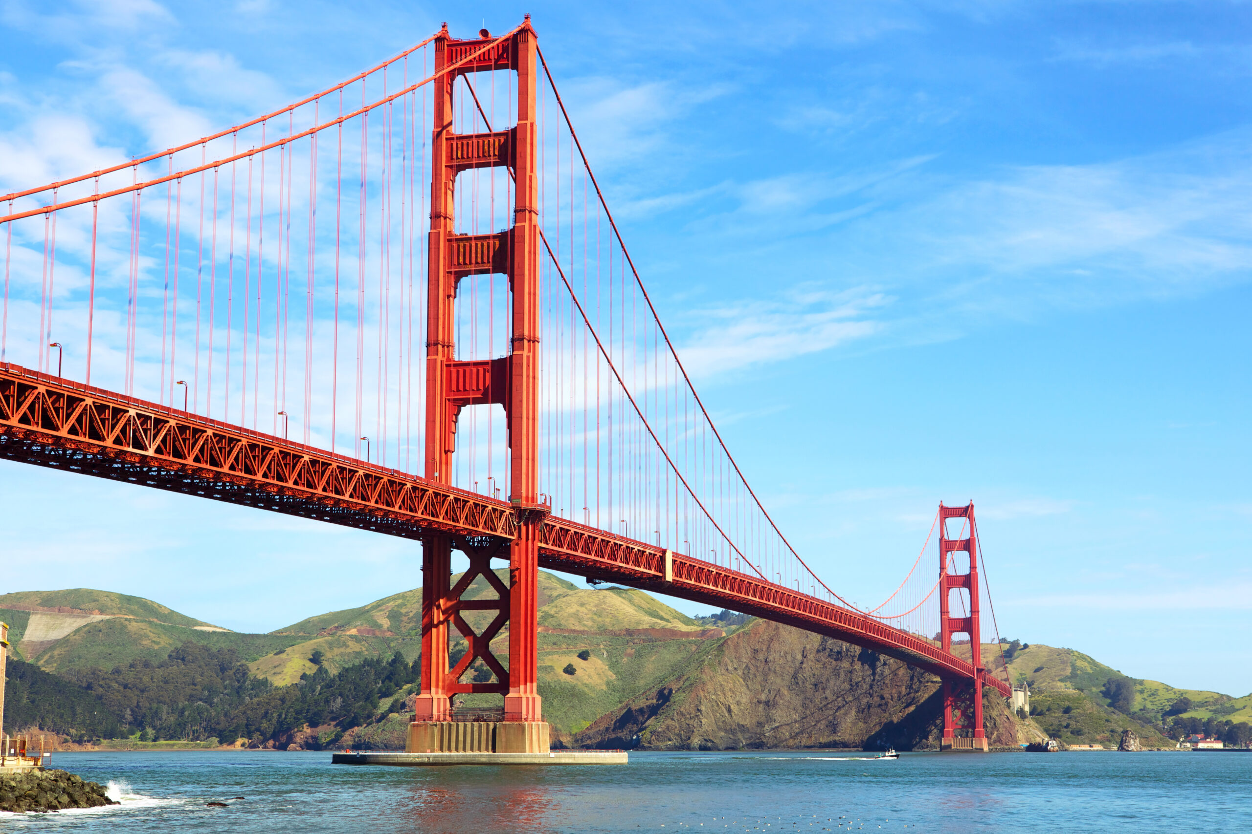 Photo of the Golden Gate Bridge with blue water underneath and gorgeous light blue sky