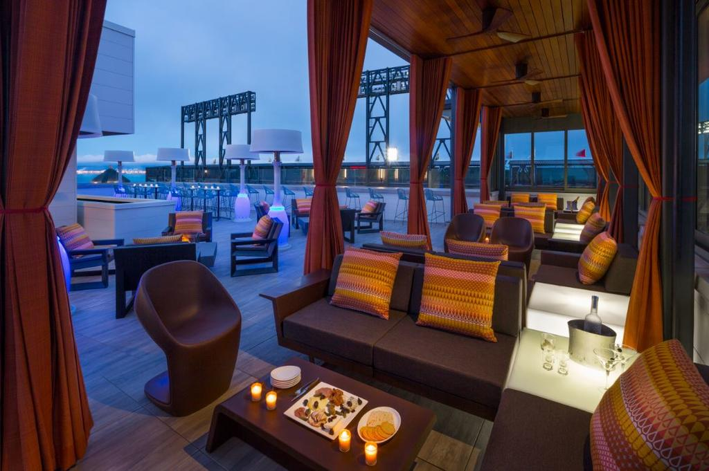 Photo of roof-top bar at Hotel Via in San Francisco. If you are looking for luxury, Hotel Via is one of the best places to stay in San Francisco. Photo features roof-top seating areas with canopy. City skyline is seen in the background.