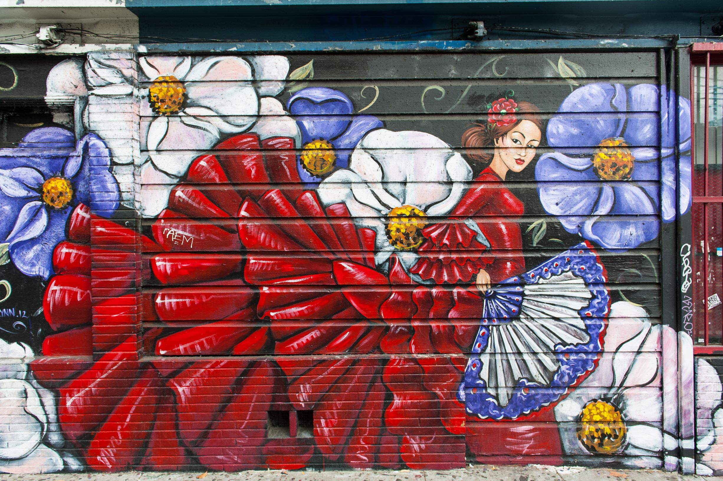 Photo of a colorful outdoor mural in the Mission District of San Francisco. Large white and purple flowers are painted around a woman in flamenco style red dress.