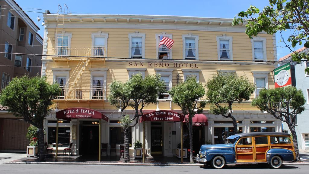 Photo of the front of San Remo Hotel in San Francisco. Features a pale yellow building with maroon awnings.