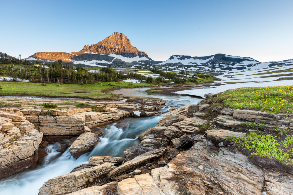 stream in foreground with light hitting a mountain in the background in Glacier national park in montana