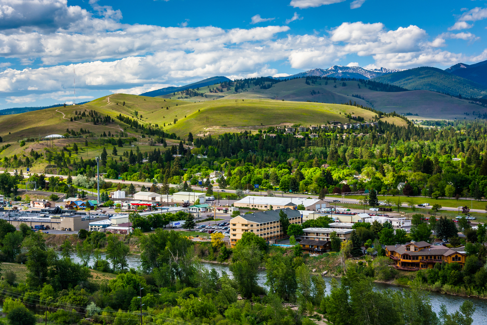Missoula Montana with a river, green trees, and a small town nestled among mountains
