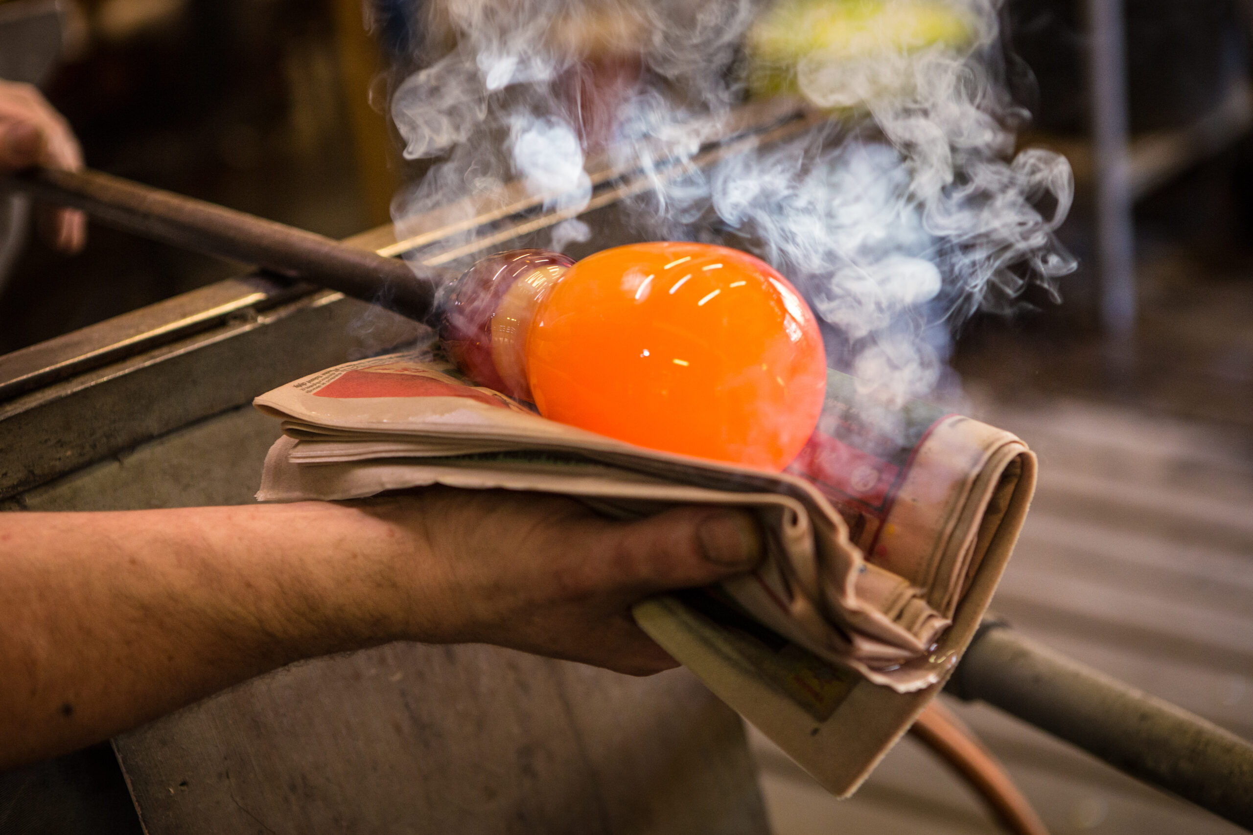 Photo of a person blowing glass.