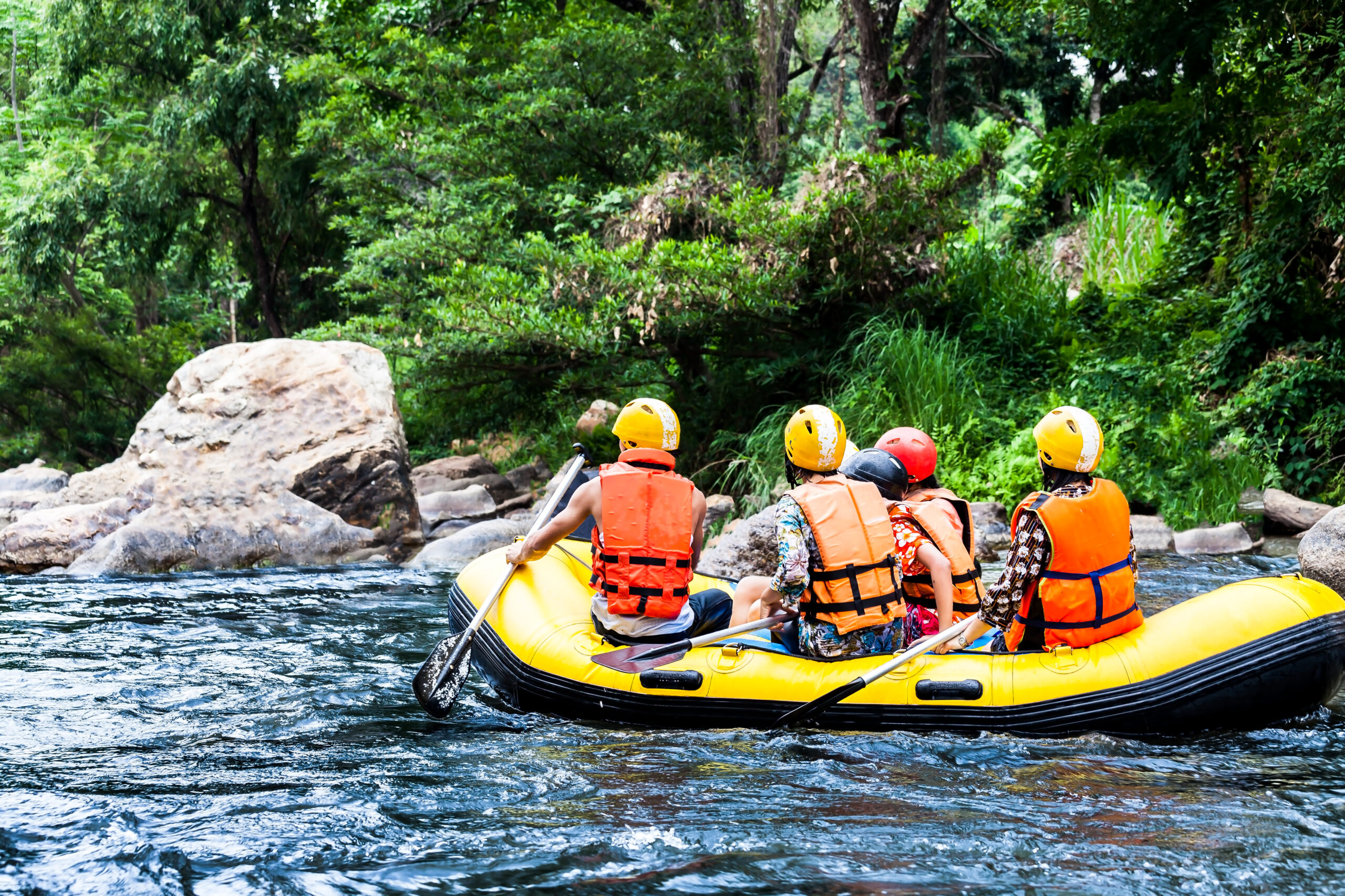 Photo of people white water rafting in a yellow rafting boat.