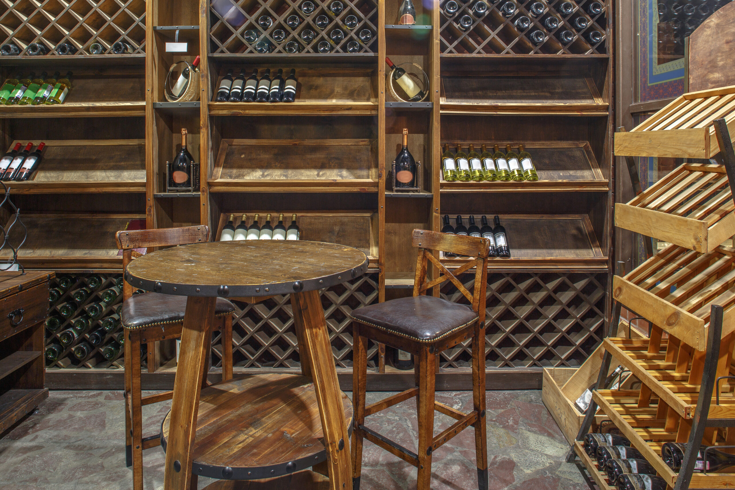 Photo of the inside of a wine tasting room featuring wine bottle of wooden racks.