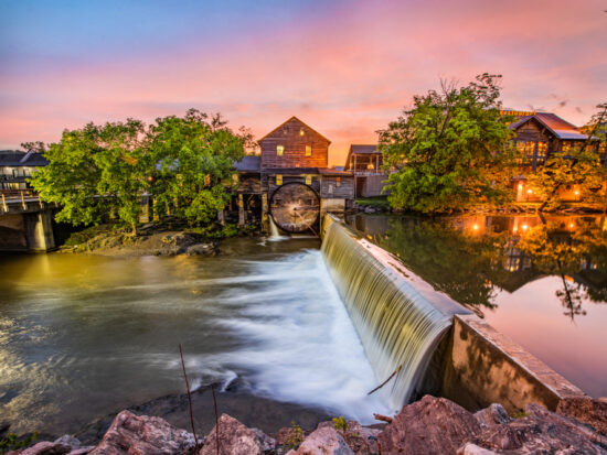 Dusk at the Old Mill, a quaint rustic building next to a small river and overflowing dam.