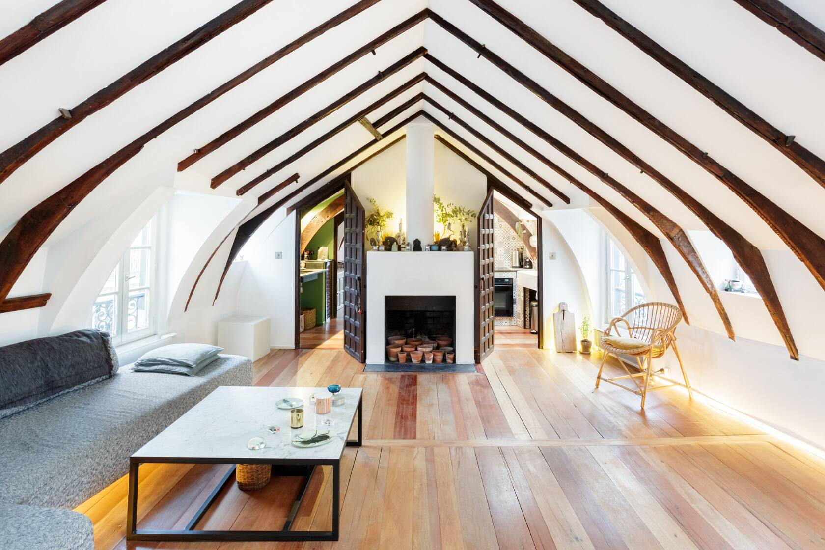 Photo of an Airbnb in Paris that is a historic loft featuring the living room with cathedral ceilings.