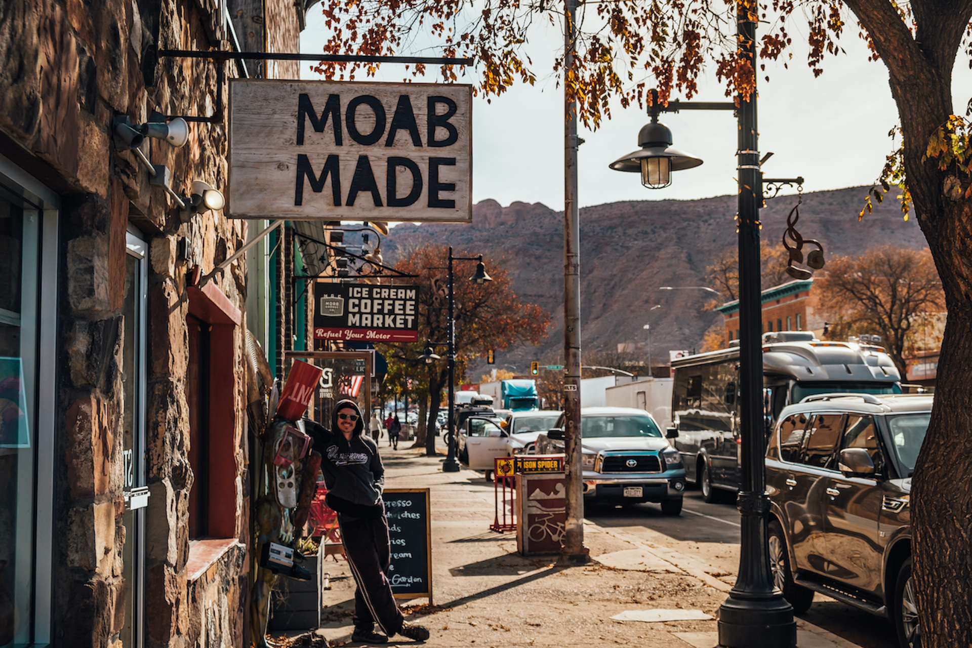 man standing in front of shop called Moab Made small towns in America