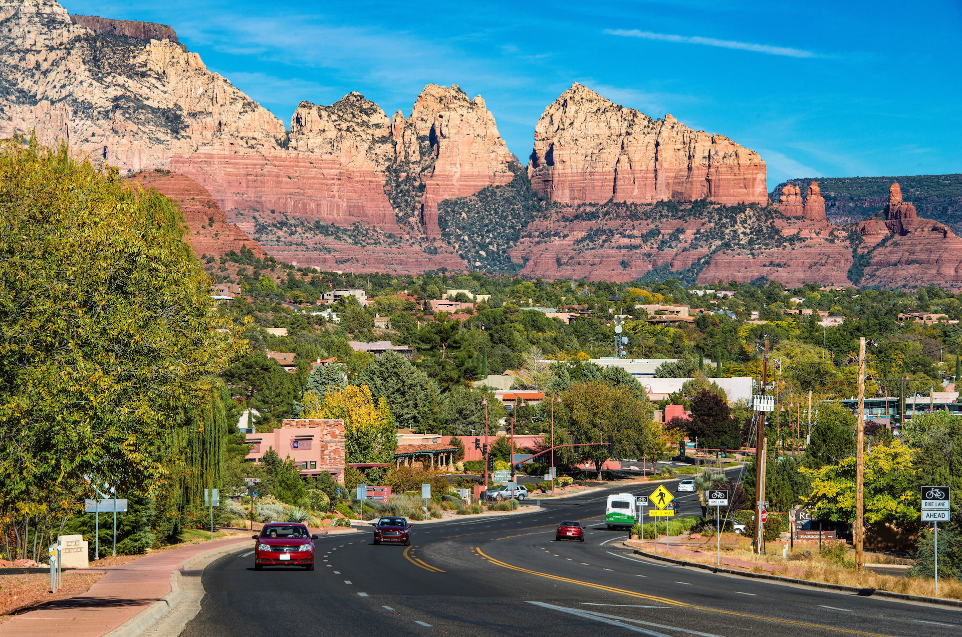 cars on road with red rocks towering in the background