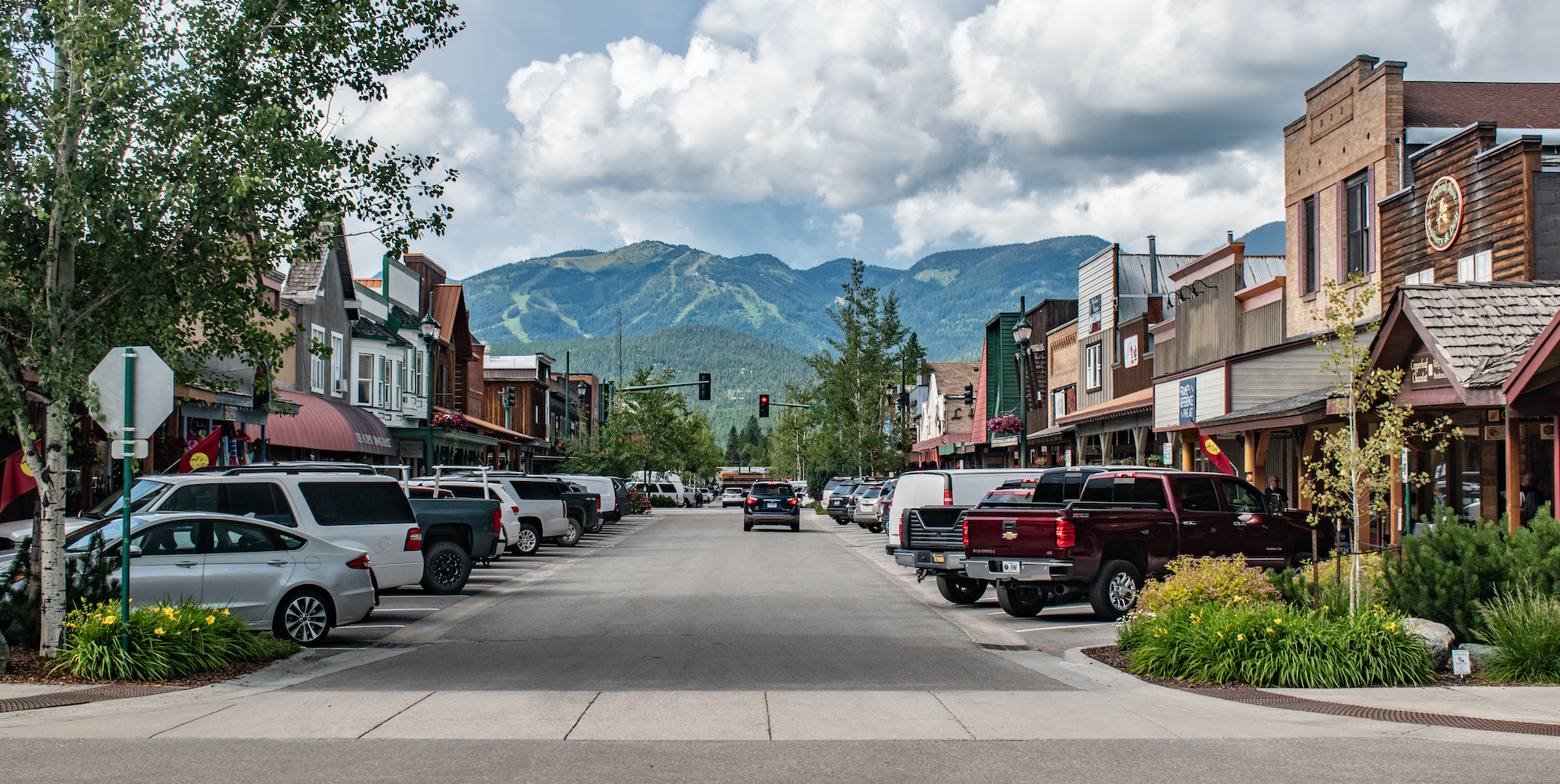 cars lining old-timey street with green mountains in the background