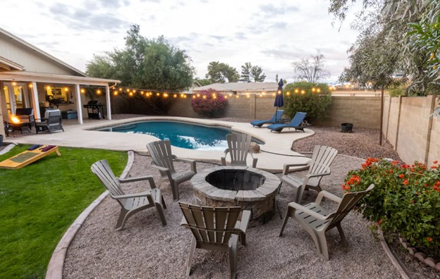 a large backyard with a large pool, string lights, a fire pit with adirondak chairs around it, and pool loungers airbnbs in arizona
