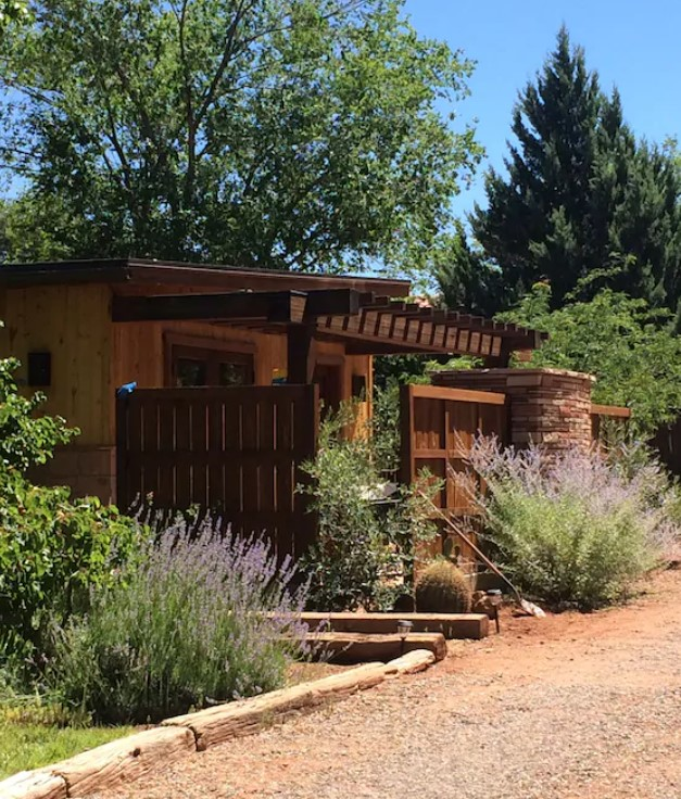 the exterior of a casita in arizona that is surround by lush vegetation, desert land, and large trees on a sunny day