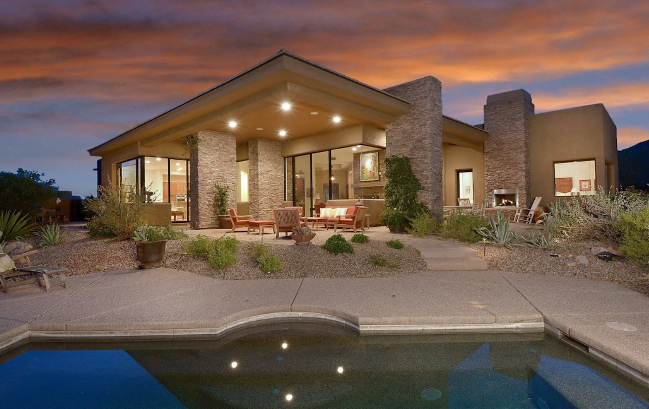 A large luxury modern home all lit up with a pool, large windows, a private patio, and desert plants at sunset