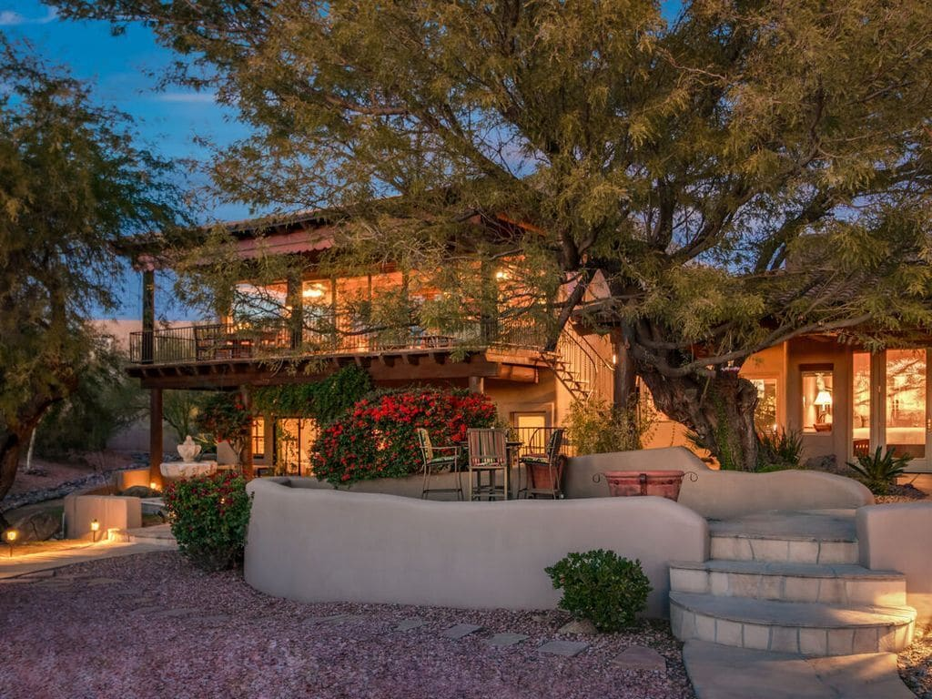The exterior of a home lit up at twilight with a large loft and covered deck on the front of the house shaded by large trees with a large desert garden