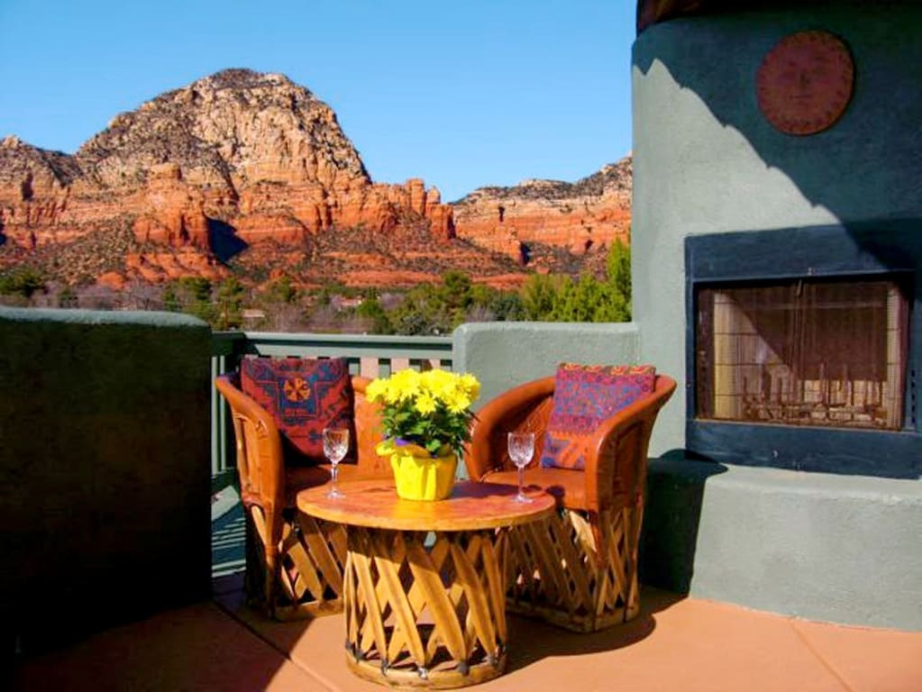 A patio with a set of colorful table and chairs with an amazing view of the Red Rocks in the background one of the best airbnbs in arizona