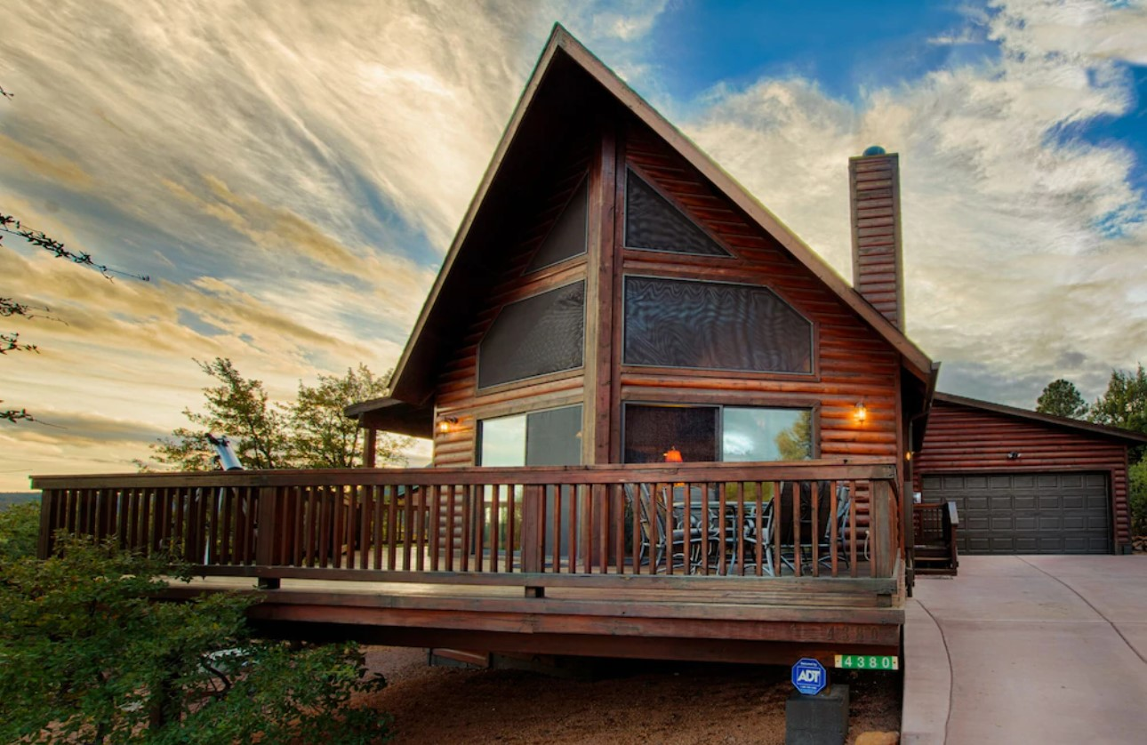 A large log a-frame cabin with a large front deck, floor to ceiling windows, and a garage on the side of it at sunset one of the best airbnbs in Arizona